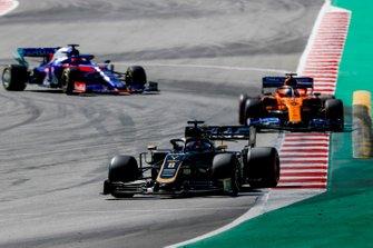 Romain Grosjean, Haas F1 Team VF-19, leads Carlos Sainz Jr., McLaren MCL34, and Daniil Kvyat, Toro Rosso STR14