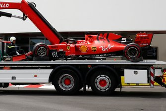 A truck returns the crashed Sebastian Vettel Ferrari SF90 back to the pit lane after FP3