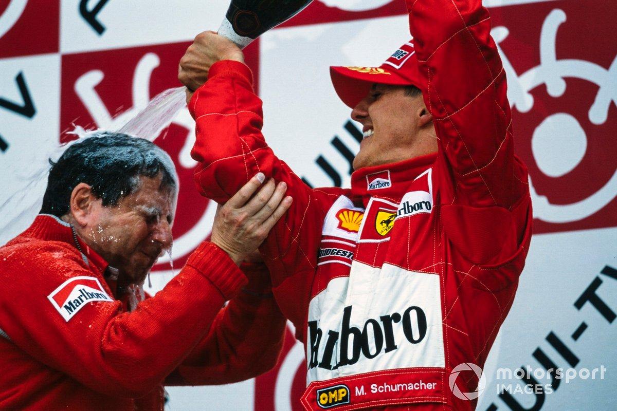 Michael Schumacher, 1er puesto, vierte champán sobre Jean Todt, director de la escudería Ferrari, en el podio después de asegurar el campeonato mundial.