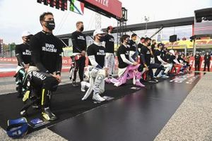 The driver stand and kneel on the grid in support of the End Racism campaign