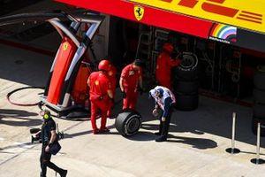Ferrari mechanics and a scrutineer with a tyre
