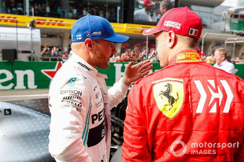 Valtteri Bottas, Mercedes AMG F1, talks to Sebastian Vettel, Ferrari, after securing pole position