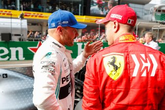 Valtteri Bottas, Mercedes AMG F1, talks to Sebastian Vettel, Ferrari, after securing pole position