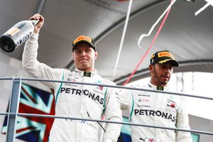 Valtteri Bottas, Mercedes AMG F1, third position, and Lewis Hamilton, Mercedes AMG F1, first position, celebrate with Champagne on the podium