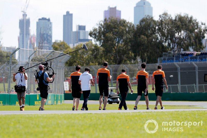 Members of the McLaren team walk the track