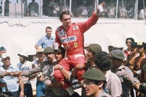 Le vainqueur Niki Lauda, Ferrari 312T, est porté à travers la foule par des soldats