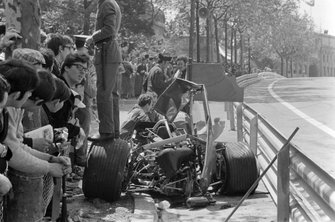 Police and Lotus mechanics guard the the wreckage of Graham Hill's Lotus 49B Ford