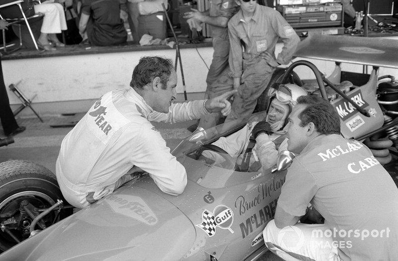 Denny Hulme habla con Bruce McLaren mientras está sentado en su Ford McLaren M14A en los pits