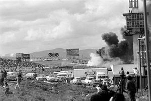 El humo sale de los restos del monoplaza de Jackie Oliver, BRM y el Ferrari de Jacky Ickx que se estrelló después de que el eje delantero de Oliver se rompiera en la primera vuelta