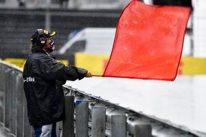 Un marshal sventola una bandiera rossa mentre la sessione viene interrotta a causa del maltempo