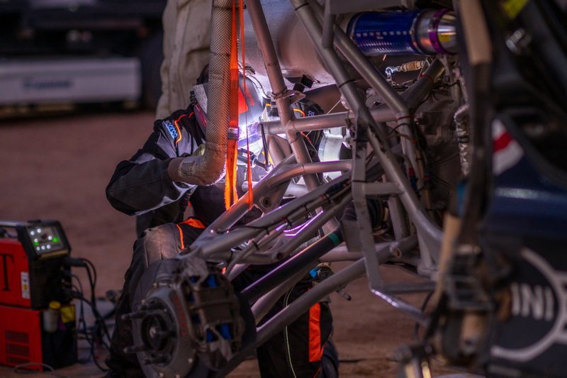 Bahrain JCW X-Raid Team mechanic works after stage