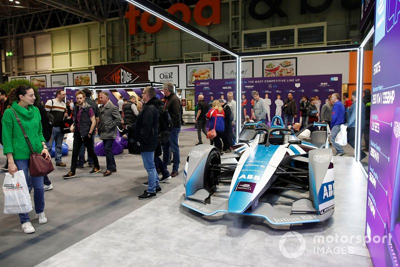 Fans admire the car on display on the Formula E stand