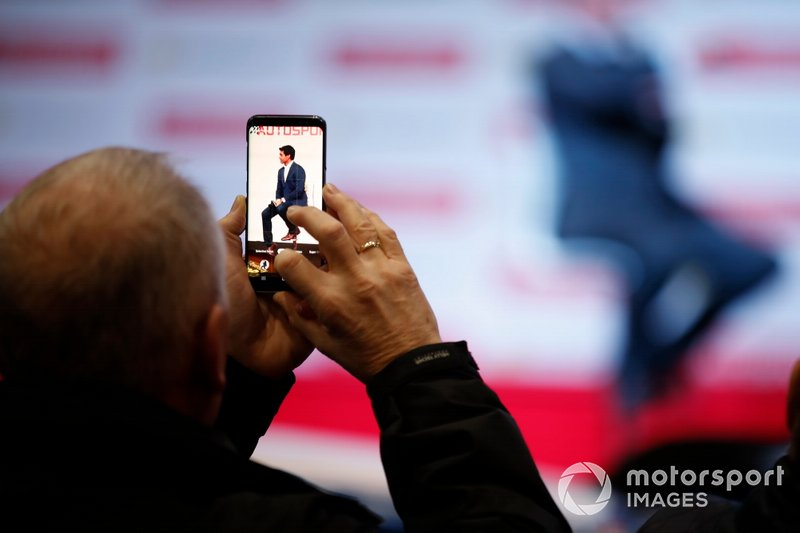 A fan takes a photo of Karun Chandhok on stage