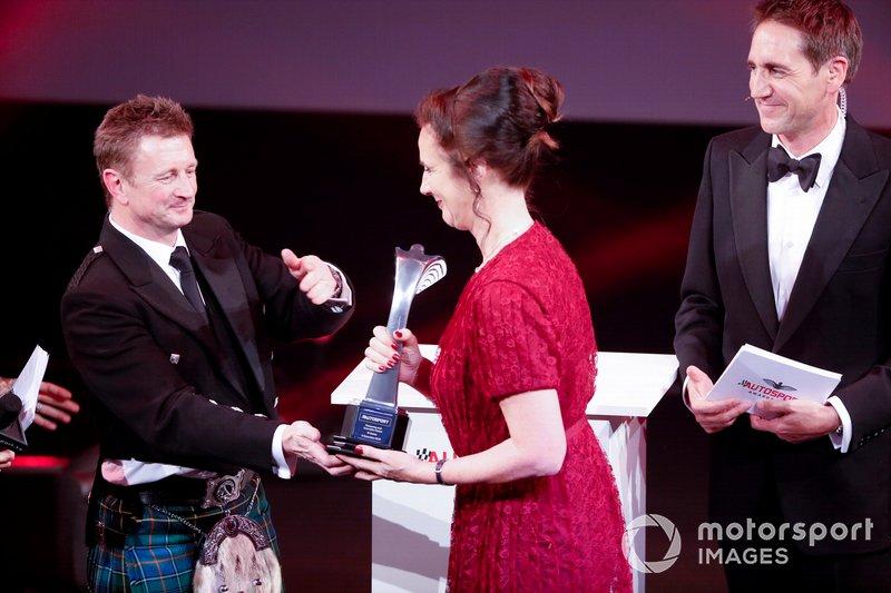 Allan McNish en el escenario para entregar el Premio Pionero y de Innovación a Catherine Bond Muir de la W Series