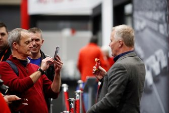 A fan takes a picture of Johnny Herbert holding a Ferrari teddy bear keyring