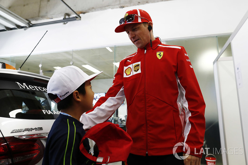 Kimi Raikkonen, Ferrari, meets a Chinese child