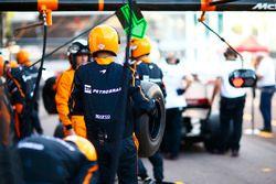 Un miembro del equipo de McLaren lleva un neumático durante la práctica de parada en boxes