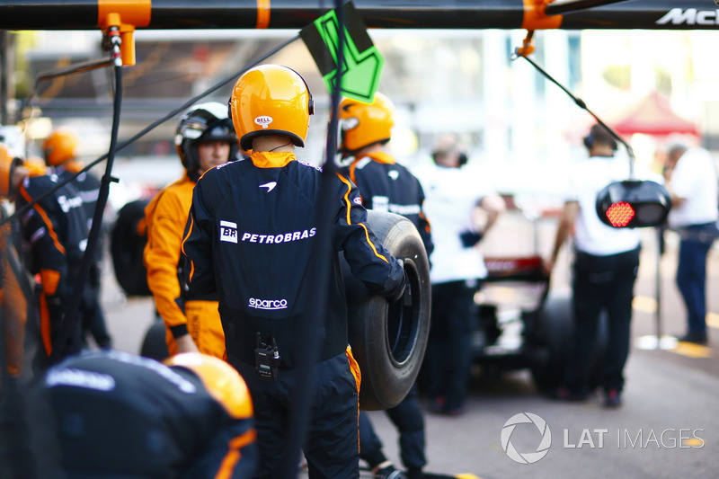 A McLaren team member carries a tyre during pit stop practice