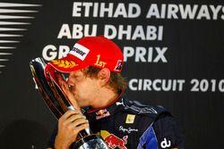 New world champion Sebastian Vettel, Red Bull Racing RB6 Renault kisses his trophy on the podium