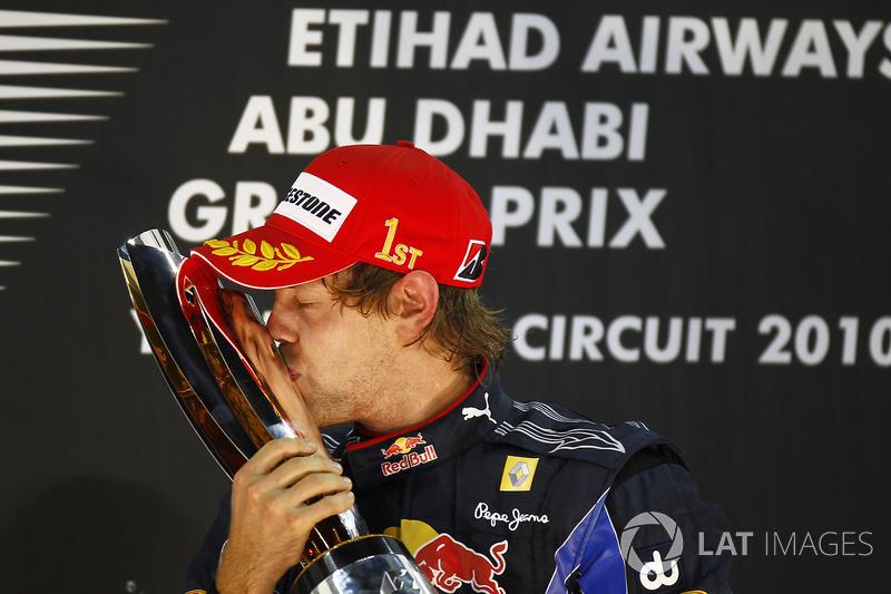 Le Champion du monde Sebastian Vettel, Red Bull Racing RB6 Renault embrasse son trophée sur le podium