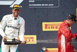 Lewis Hamilton, Mercedes AMG F1, 1st position, sprays Champagne on the podium at Kimi Raikkonen, Ferrari, 3rd position, on the podium