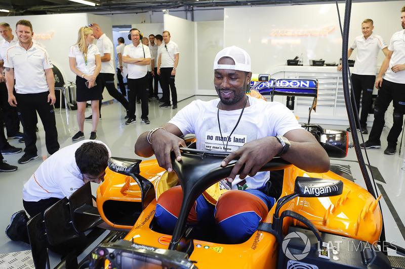 El jugador de baloncesto Serge Ibaka, de los Toronto Raptors en NBA e internacional con España, se intenta sentar en el McLaren de Fernando Alonso