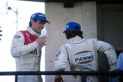 Een uitgeputte winnaar Gilles Villeneuve, Ferrari, en John Watson, McLaren, wachten op het podium voor de Spaanse Koning Juan Carlos