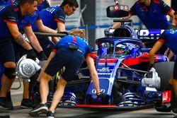 Degli ingegneri Toro Rosso spingono Brendon Hartley, Toro Rosso STR13 Honda, nel garage