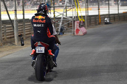 Max Verstappen, Red Bull Racing crashed in Q1 and is given a lift on a motorbike