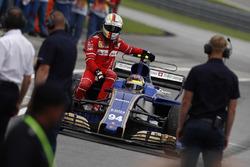 Sebastian Vettel, Ferrari, rides back to the pits on the sidepod of the Pascal Wehrlein Sauber C36