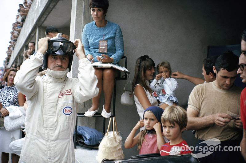 Graham Hill se prepara para competir en boxes, rodeado de su familia: su esposa Bette Hill y una niñera que cuida a los tres niños - más adelante F1 mundo campeón Damon