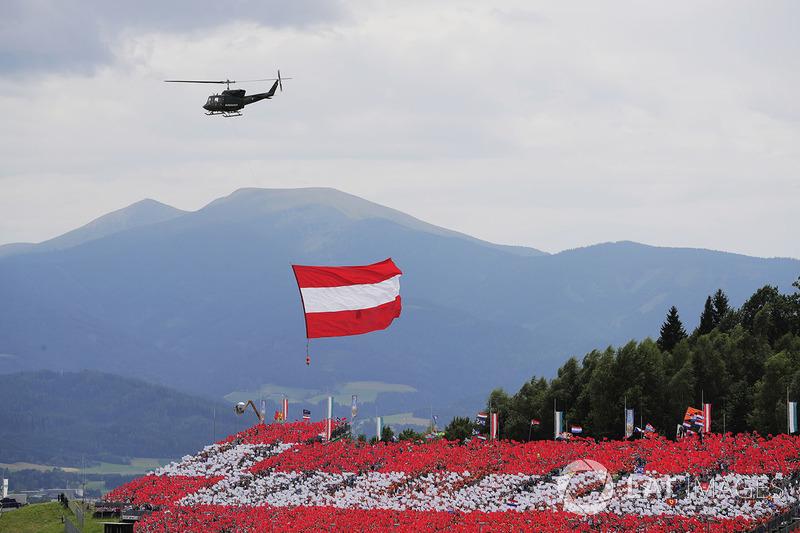 Австрійський прапор на гелікоптері, що летить над трибуною з місцевими уболівальниками