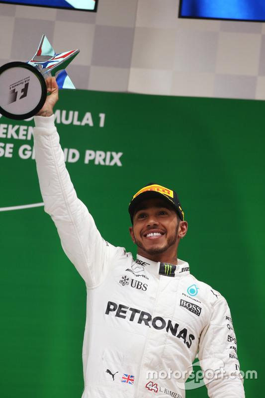 Lewis Hamilton, Mercedes AMG, celebrates on the podium with his trophy