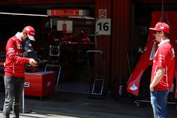 Sebastian Vettel, Ferrari, takes a picture of Kimi Raikkonen, Ferrari, on a vintage camera in the pi