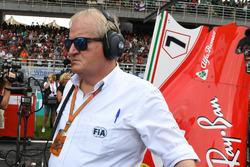 Технический делегат FIA Джо Бауэр наблюдает за механиками Ferrari возле автомобиля SF70H Кими Райкко