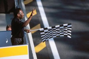 Pele holds the chequered flag