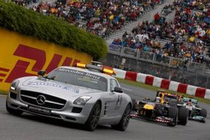 The Mercedes AMG safety car leads Sebastian Vettel, Red Bull RB7 Renault, Michael Schumacher, Mercedes MGP W02, and Mark Webber, Red Bull RB7 Renault