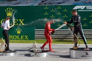 Charles Leclerc, Ferrari, and Valtteri Bottas, Mercedes AMG F1, celebrate with champagne on the podium