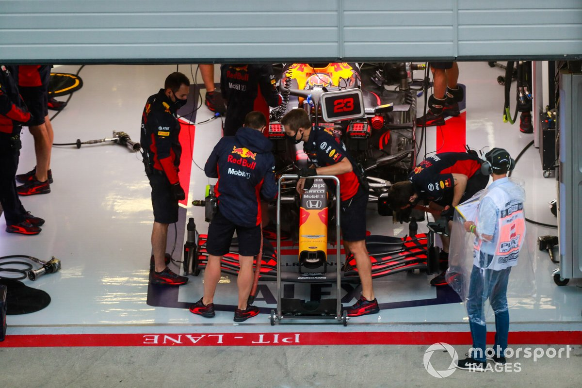 The Alexander Albon Red Bull Racing RB16 is worked on by mechanics in the team's garage