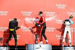 Callum Ilott, UNI-Virtuosi, 1st position, Christian Lundgaard, ART Grand Prix, 2nd position, and Jack Aitken, Campos Racing, 3rd position, celebrate with Champagne on the podium
