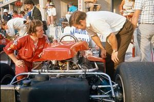 Dick Scammell of Lotus stands over the Jochen Rindt Lotus 72C Ford, Rindt can be seen behind, close to the cockpit of team-mate John Miles