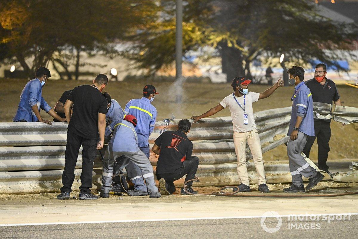 Los oficiales retiran los restos después del choque de Romain Grosjean, Haas VF-20, en la primera vuelta
