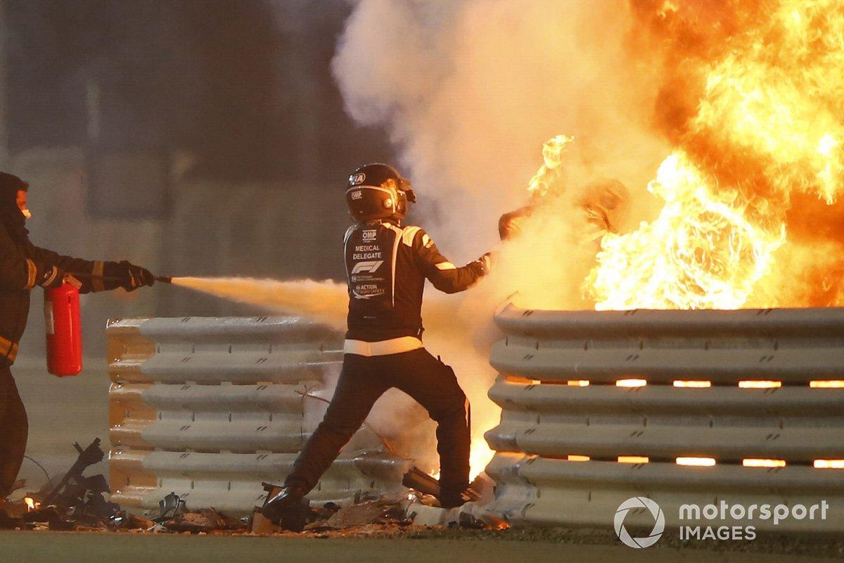 Petugas medis menyemprot pemadam api ke tubuh pembalap Haas, Romain Grosjean