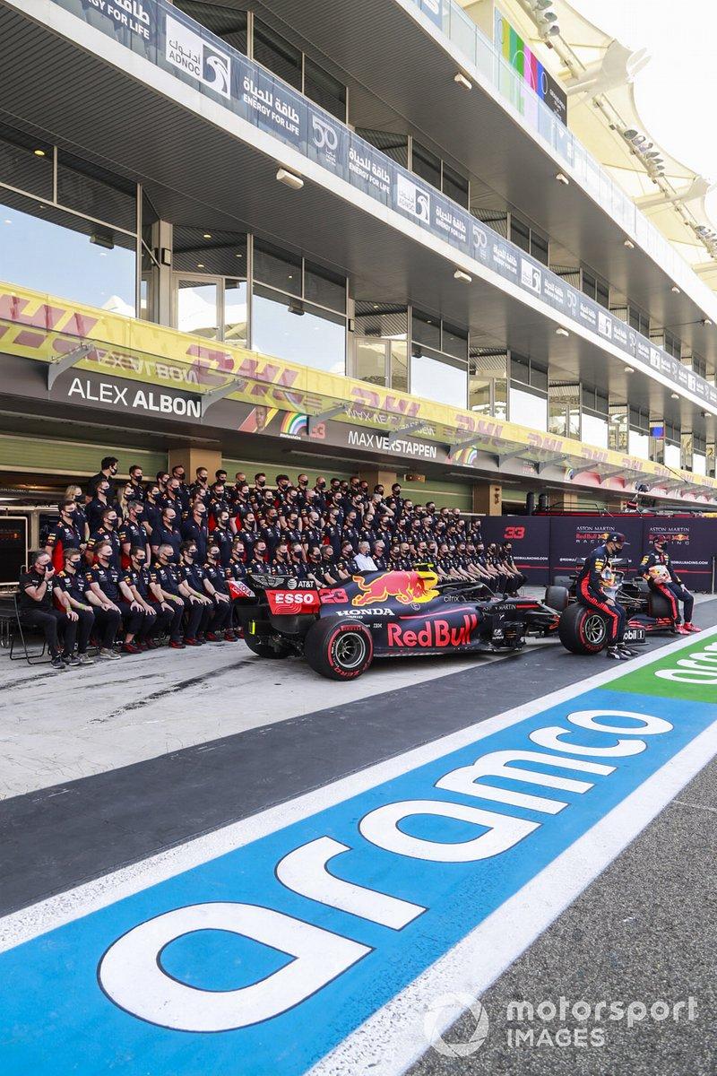 Foto de grupo del equipo Red Bull con Alex Albon, Max Verstappen y sus coches en el pitlane