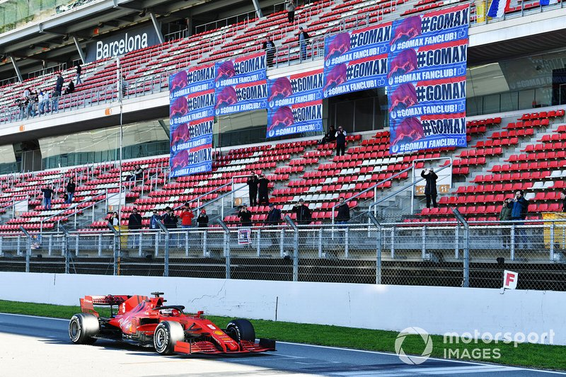 Sebastian Vettel, Ferrari SF1000, passes a stand showing banners in support of Max Verstappen, Red Bull Racing
