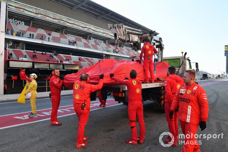 Sebastian Vettel, Ferrari, is lifted back into the garage after stopping on track