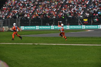 Marshals retrieve some debris from the track