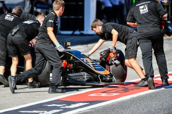 Kevin Magnussen, Haas F1 Team VF-19, is returned to the garage with front wing and other damage