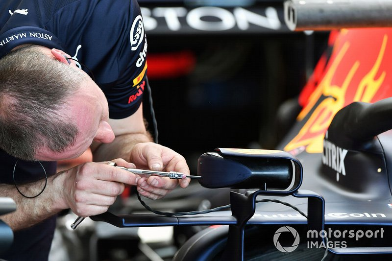 An engineer adjusts a wing mirror on the Red Bull Racing RB15