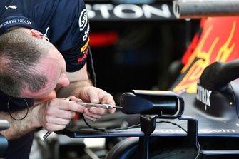 Un ingegnere sistema uno specchietto sulla Red Bull Racing RB15